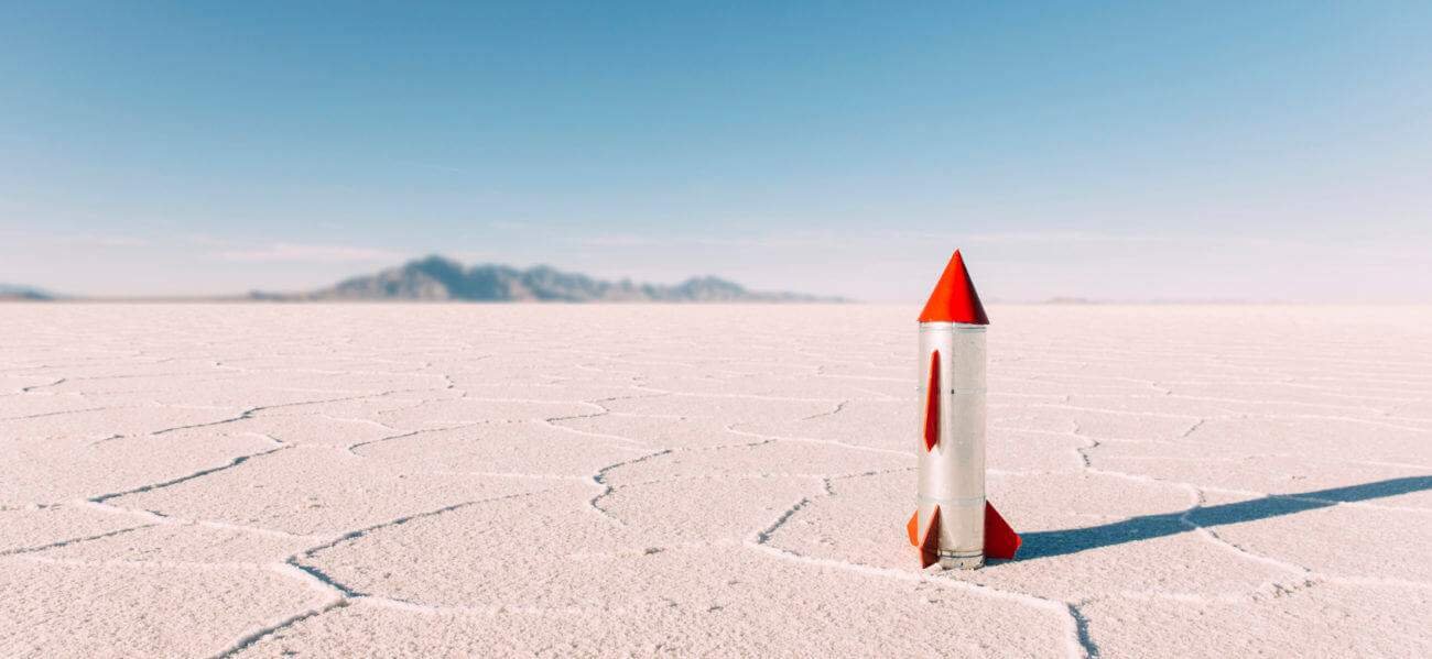 A generic homemade rocket sits on the Bonneville Salt Flats located in Utah, USA. No people are in the picture. The sky is blue and there is lots of copy space.